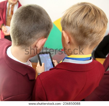 schoolboys play on the tablet - stock photo