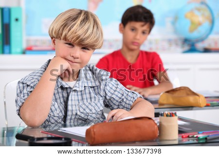 schoolboys seated at desk in classroom - stock photo