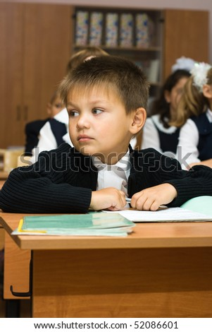 Schoolboys sit in a class room. One child looks aside - stock photo