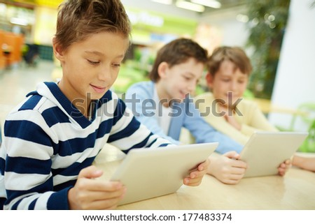 Schoolboys studying with touchpads - stock photo