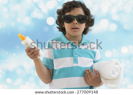 Schoolchild boy ready to go to the beach . Boy holding  sun tan lotion bottle. and rolled towel - stock photo