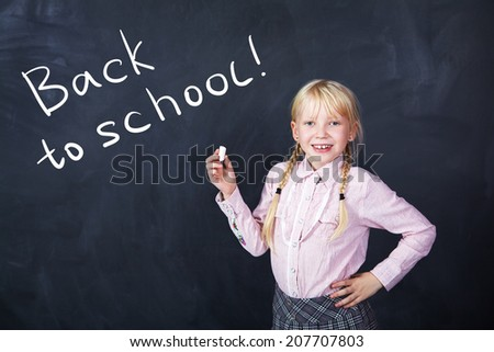 schoolchild with chalk in hand on a background of the board. School and education