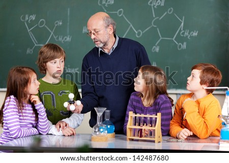 Schoolchildren and teacher in a science class - stock photo