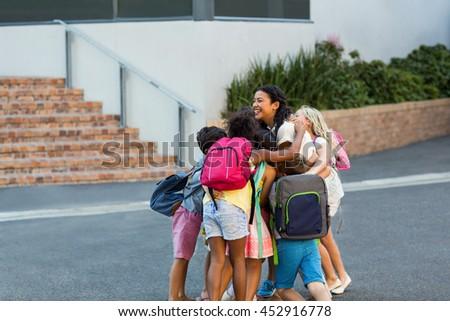 Schoolchildren embracing happy teacher outside school - stock photo