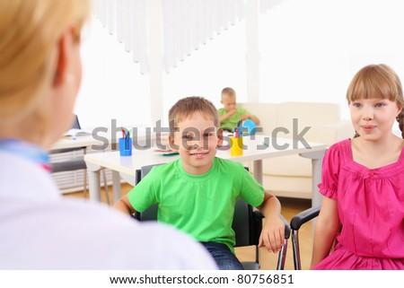 Schoolchildren listen to their teacher at the school. Schoolchildren sit a half-circle - stock photo