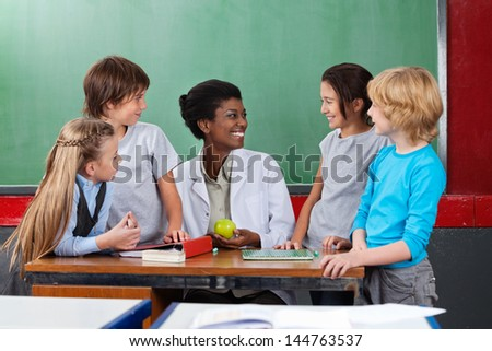 Schoolchildren looking young African American teacher sitting at desk in classroom