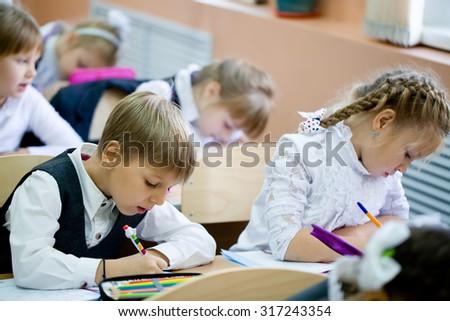 schoolchildren sit at their desks in elementary school - stock photo