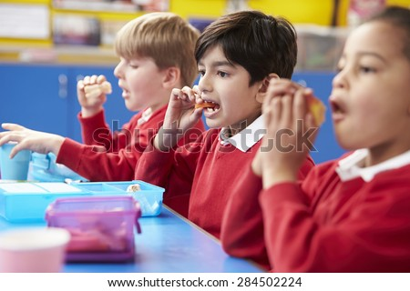 Schoolchildren Sitting At Table Eating Packed Lunch - stock photo