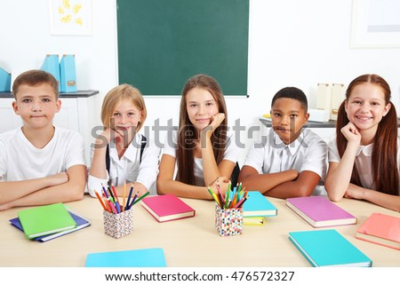 Schoolchildren sitting at table in classroom