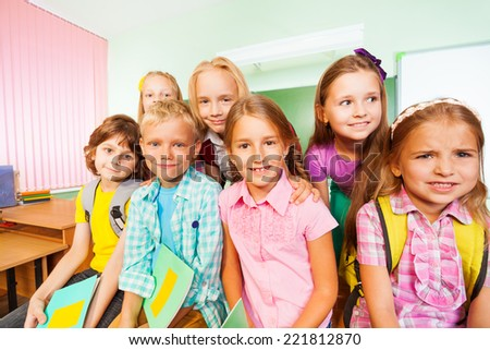 Schoolchildren sitting close near desk and smile