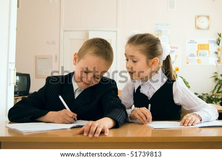 schoolchildren sitting in classroom and writing - stock photo
