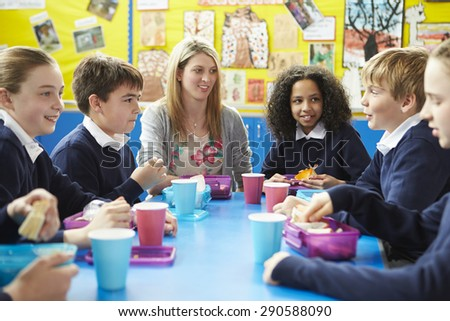 Schoolchildren With Teacher Sitting At Table Eating Lunch - stock photo