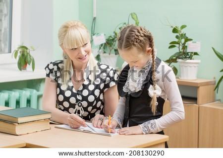 schoolgirl and teacher in classroom - stock photo