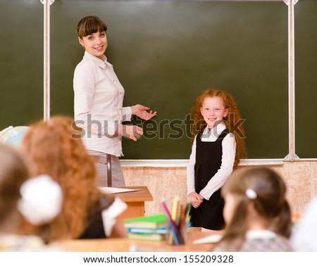 schoolgirl and teacher near a school board - stock photo