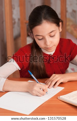 Schoolgirl doing homework at the table