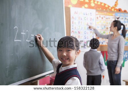 Schoolgirl doing math equation on the black board