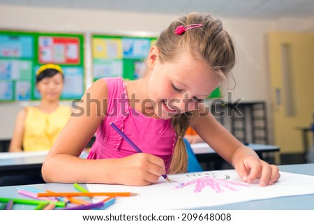 Schoolgirl drawing with crayon at lesson - stock photo