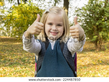 schoolgirl holding book and smiling in the park - stock photo