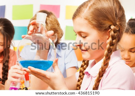 Schoolgirl holding flask with blue reagent at lab
