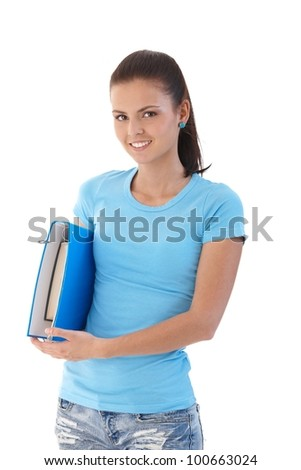 Schoolgirl holding folder, smiling, looking at camera. - stock photo