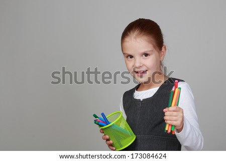 Schoolgirl holding pens for drawing/Happy child play with colorful felt tip pens and smile on gray background - stock photo