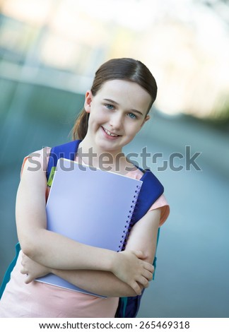 Schoolgirl in a blue shirt with a purple backpack ready for school - stock photo
