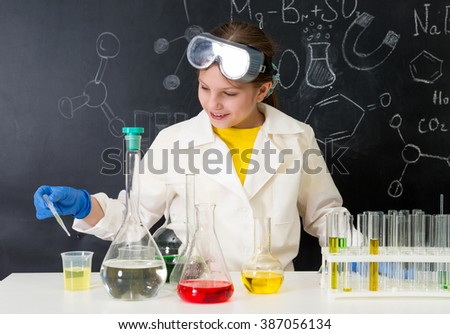schoolgirl in white gown doing experiments with liquids in chemistry lab - stock photo