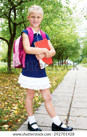 Schoolgirl is on the way to school for the first time. ?ute schoolgirl in blue dress is going to school for the first time - stock photo