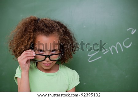 Schoolgirl looking above her glasses in front of a blackboard - stock photo