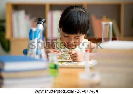 Schoolgirl looking at the sketch through magnifier glass - stock photo