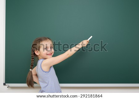Schoolgirl near the school board - stock photo