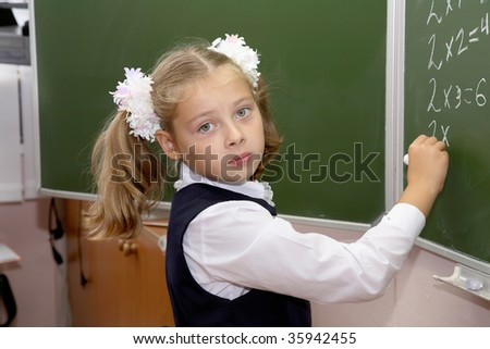 schoolgirl of an elementary grade answers at a board