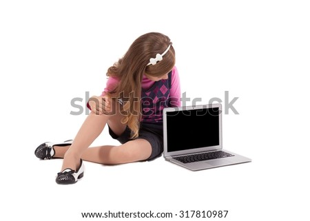 schoolgirl on a white background looking into the laptop and smiling, picture with depth of field and artistic blur