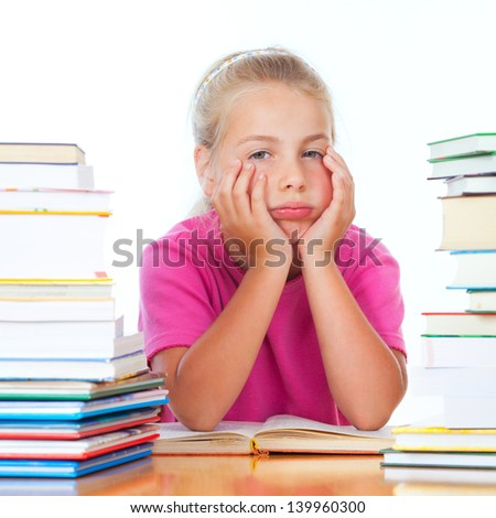 schoolgirl on desk frustrated of the many books - stock photo