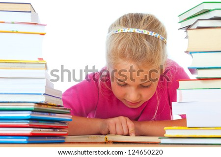 schoolgirl on desk reading a book between many books