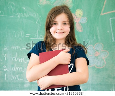 Schoolgirl on school board with book posing - stock photo