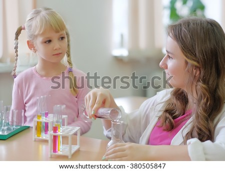 Schoolgirl or student shows experiment for the  little girl
