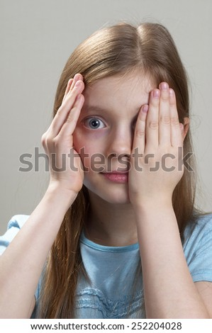 Schoolgirl peeping through hand with one eye over grey background - stock photo