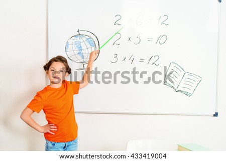 Schoolgirl performs the tasks at the blackboard in the classroom. Education. - stock photo