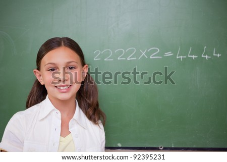 Schoolgirl posing in front of a chalkboard in a classroom - stock photo