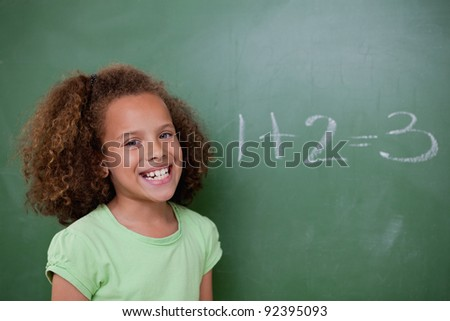 Schoolgirl posing in front of an addition on a blackboard - stock photo