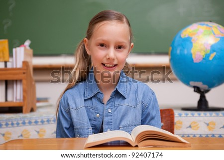 Schoolgirl reading a book in a classroom - stock photo