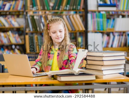 Schoolgirl reading a book in the library - stock photo