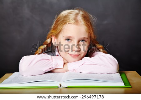 schoolgirl reading a book. School and education. a child learns in school