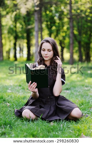 Schoolgirl reading a book sitting on the grass. Beautiful girl reading a book
