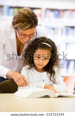 Schoolgirl reading a book with the guidance of her teacher - stock photo