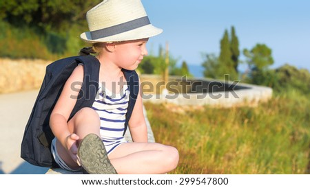 Schoolgirl Returning to school after the holidays, smiling and cheerful, with a rucksack - stock photo