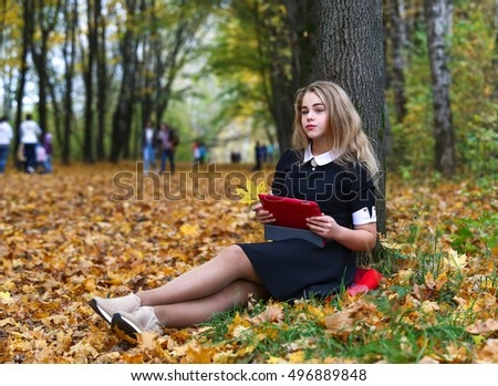 Schoolgirl sitting in the autumn park and holding a digital tablet in hands
