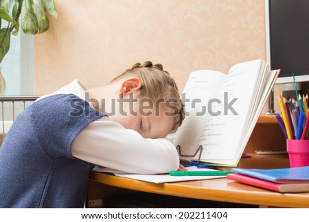 Schoolgirl sleeping on books sitting at the table - stock photo