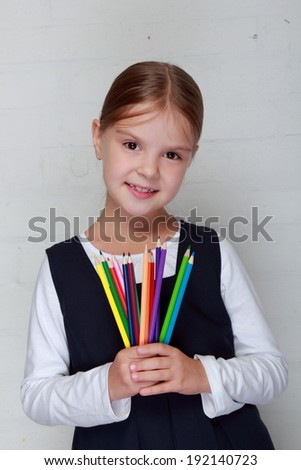 schoolgirl smiling happily on Education theme/Lovely little schoolgirl holds a pencil